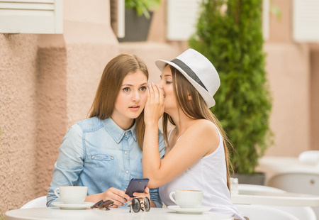 gossiping: Two beautiful young women sitting at summer cafe, drinking hot coffee and gossiping.