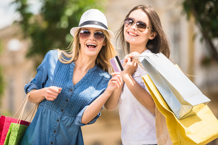 gift spending: Young girls with shopping bags looking at camera and smiling. Blond hair woman holding credit card.