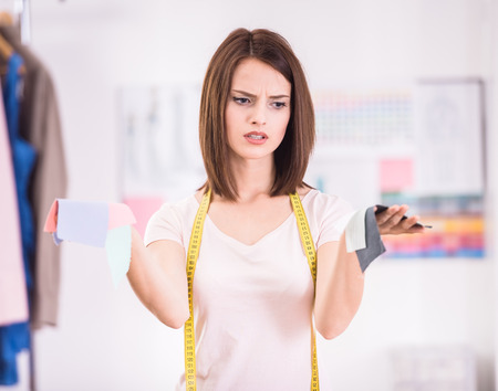 difficult decision: Difficult decision. Female fashion designer choosing what kind of fabric to use. Stock Photo