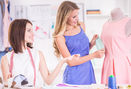 working dress: Beautiful fashion designers working at pink dress in studio. Stock Photo