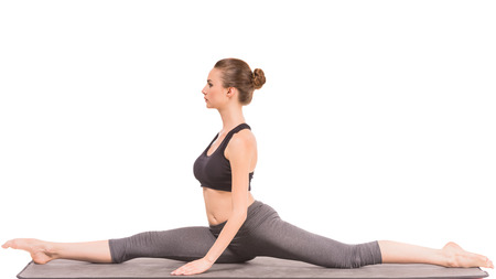 the split: Beautiful slim woman doing yoga exercise, sitting on the splits over white background. Stock Photo
