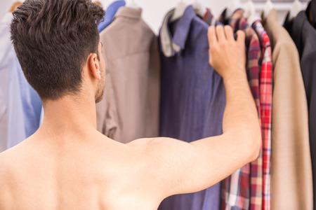 choosing clothes: Young man choosing clothes on a rack in wardrobe. Back view. Stock Photo