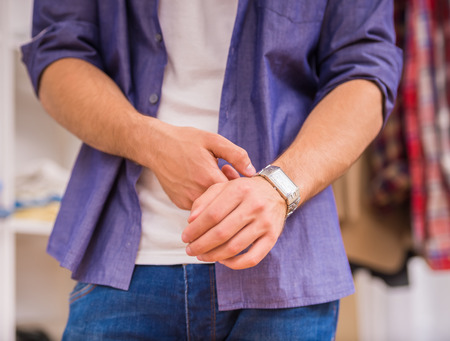fastening: Young man in shirt fastening wristwatch in dressing room. Stock Photo