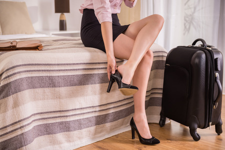 suit case: Business woman taking down her shoes while sitting on bed near suit case at the hotel room. Close-up. Stock Photo