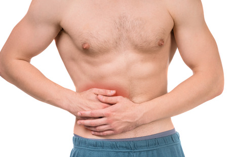 abdominal pain: Muscular man has strong abdominal pain  over white background, studio shot. Close-up. Stock Photo