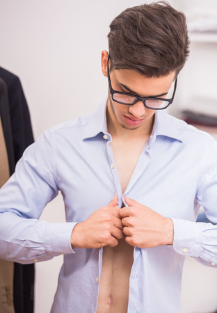 Concentrated man in glasses dressing blue shirt in dressing room. Stock Photo