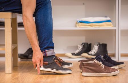 piernas hombre: Primer plano del hombre pone en los zapatos en el camerino. Foto de archivo