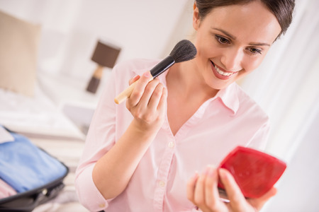 apply: Business woman applying make-up while sitting on bed at the hotel room.