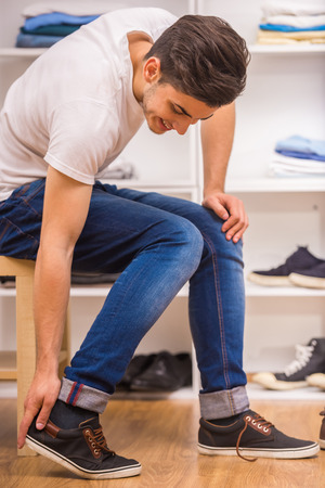 formal dressing: Handsome man putting on shoes while sitting on chair at the dressing room. Stock Photo