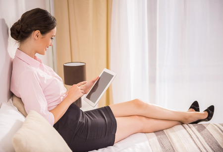scrolling: Business lady working with her digital tablet and lying on bed at the hotel room. Side view.