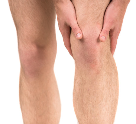 Man having knee pain, studio shot over white background. Close-up.