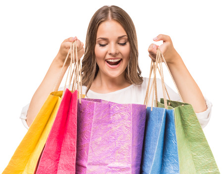 looking inside: Beautiful woman looking inside shopping bags on white background.