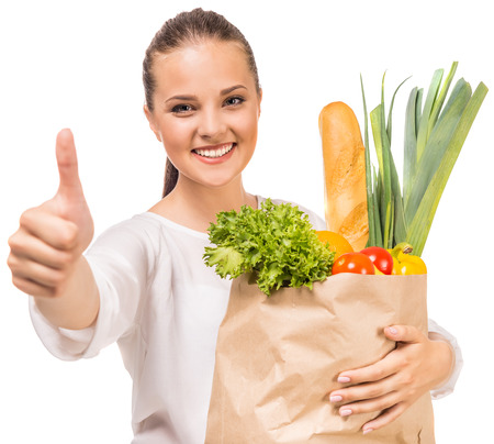 happy customer: Cheerful woman showing thumb up and holding shopping bag full of fresh food on white background.