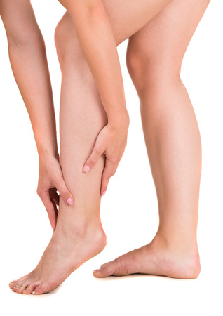 touching toes: Woman having leg pain, studio shot over white background. Side view. Close-up.