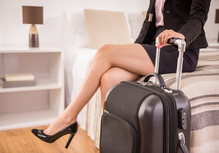 only women: Business woman holding suitcase while sitting on bed at the hotel room. Close-up.