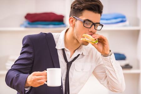 Hombre con estilo en gafas de comer su breackfast mientras hurring funcione.