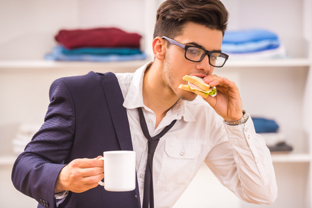 eating up: Stylish man in glasses eating his breackfast while hurring to work. Stock Photo