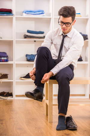 Stylish man in glasses tying shoe laces while sitting on chair at the dressing room. Stock Photo