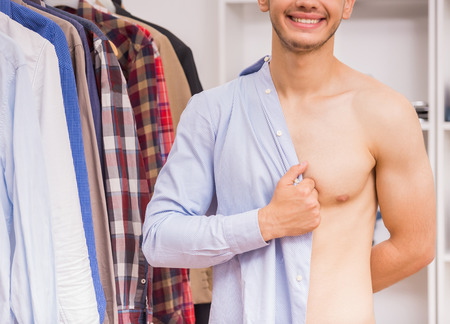 formal dressing: Cheerful young man dressing blue shirt in dressing room. Close-up. Stock Photo