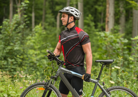 road side: Young man in helmet standing with mountain bicycle near the forest road. Side view. Stock Photo