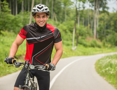 road cycling: Young man in helmet riding on mountain bicycle on the forest road.