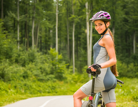 road cycling: Attractive girl standing with bicycle on the forest road, looking at camera and smiling. Stock Photo