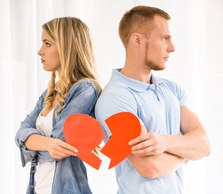 Rift en las relaciones. Pareja joven triste celebración de corazón roto.
