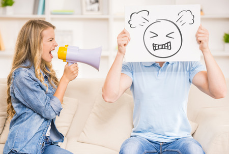 mouthpiece: Wife shouting on her husband with mouthpiece while he holding image of angry face. Stock Photo