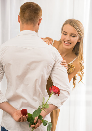 looking behind: Man making surprise. His wife looking behind his shoulder what he want to present. Stock Photo