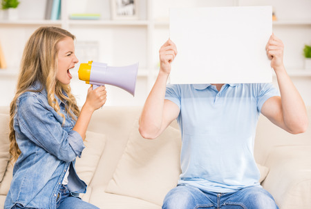 mouthpiece: Wife shouting on her husband with mouthpiece while he closing his face with piece of paper. Stock Photo