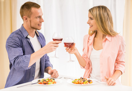romantic man: Beautiful family couple having dinner together. They are drinking wine and looking to each other in kitchen. Stock Photo