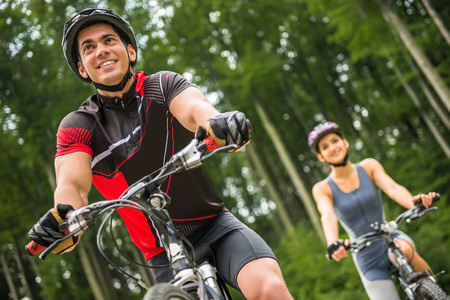 Young sporty couple riding on bicycles at the forest road. Man in front of woman.