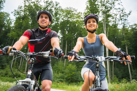 Happy carefree bike couple cycling outdoors and leading healthy lifestyle.