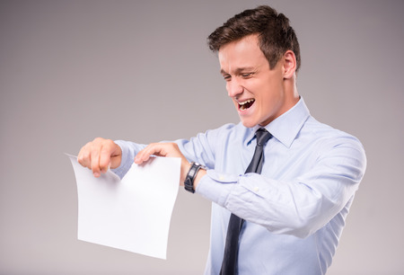 emotional: Emotional young businessman tearing paper on a gray background Stock Photo