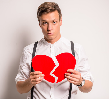 Young man on a gray background holding paper broken heart