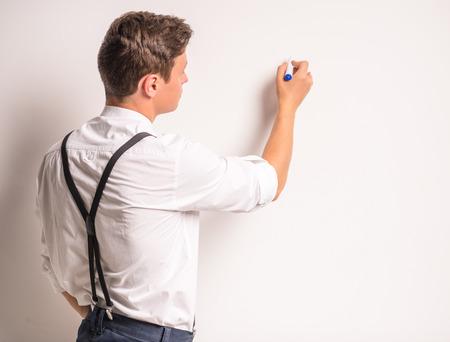 Portret van een jonge zakenman, schrijf een marker op de muur