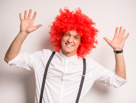 red shirt: Portrait of a happy young man in a red wig Stock Photo