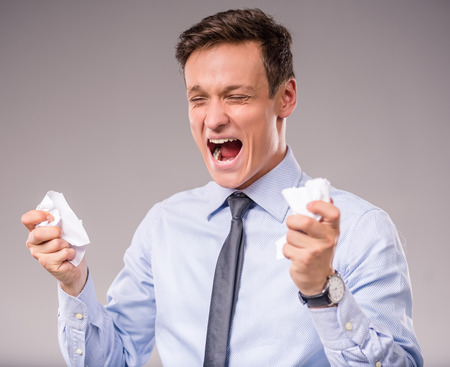 tearing: Emotional young businessman tearing paper on a gray background Stock Photo