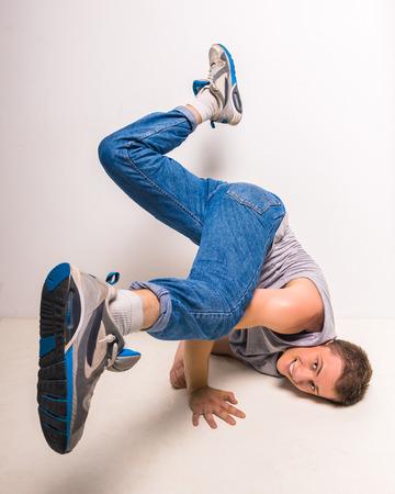 breakdancer: Skilful breakdancer posing on his hands at studio over white background.