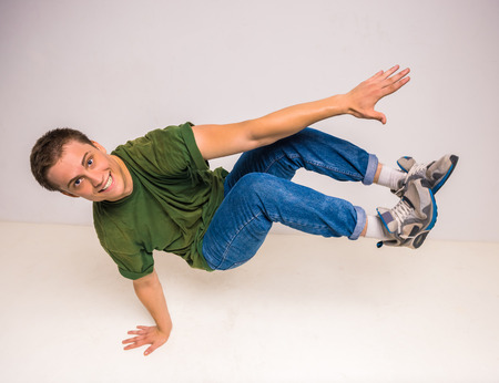 breakdancer: Skilful breakdancer doing moves while performing a handstand over white background.