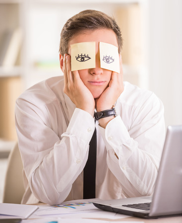 Tired businessman with adhesive note on his eyes. Concept of sleeping.