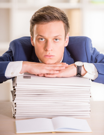 tired businessman: Tired businessman is sitting with a lots of folders.