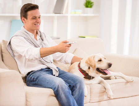 dog pose: Young smiling man is sitting on sofa with dog and watching tv.