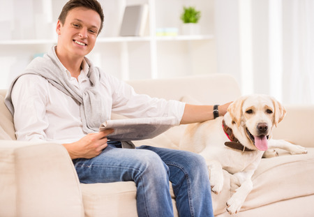 doggie: Young smiling man is sitting on sofa with dog and holding a newspaper.
