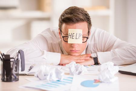 Gefrustreerd jonge zakenman in zijn kantoor met zelfklevende notitie op zijn voorhoofd. Hij heeft hulp nodig.