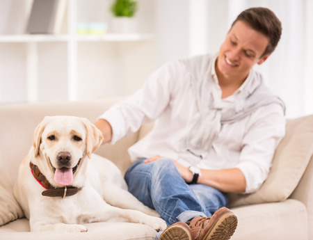 Young smiling man is playing with his dog sitting on sofa. Banco de Imagens