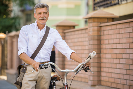 vertica: Senior man with his bike in the street, in town. Concept of active life elderly people.