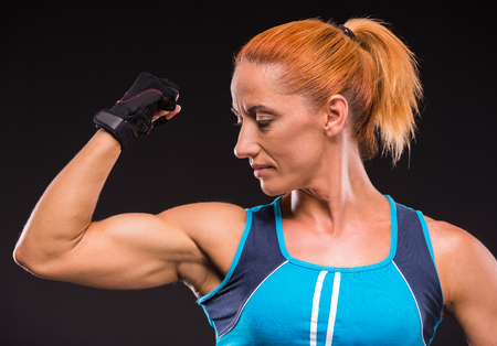showing muscles: Athletic woman showing muscles of the hands on a dark background.