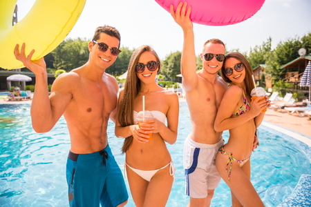 Beautiful young people having fun in swimming pool with colored rubber rings. Stock Photo