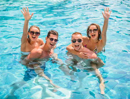 splash pool: Beautiful young people having fun in swimming pool, smiling. Stock Photo
